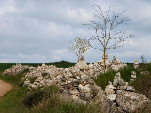 Trees and stone shrines on the great wide expanse of the Meseta
