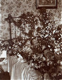 Deceased child surrounded by flowers. Image Source BBC.